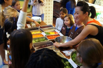 JUCCCE Project Director Lucy Luo shows Girl Scouts how they can make a healthy, sustainable meal from the assembled foods